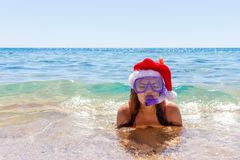 Snorkel girl with glasses, tube and Santa Claus hat for swimming on summer vacation stock photography