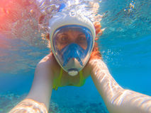 Snorkel girl underwater selfie. Snorkeling in full face mask. Summer activity. Beautiful girl in sea water. Underwater photo of diving person. Active vacation Stock Photos
