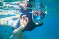Snorkel girl underwater shows ok gesture. Snorkeling in full face mask. Royalty Free Stock Images