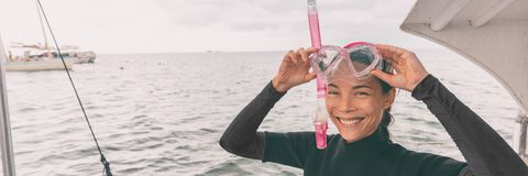 Snorkel mask Asian woman tourist getting ready for snorkeling activity tour from boat banner. Panorama royalty free stock photos