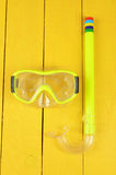 Snorkel and mask for diving isolated on yellow wooden background Royalty Free Stock Image