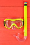 Snorkel and mask for diving on red wooden background Royalty Free Stock Photos