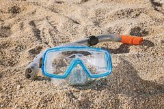Snorkel mask with tube on sandy beach. Blue Snorkel mask with tube on sandy beach, close up Stock Images