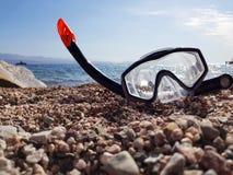 Snorkel- och dykapparatmaskering på stranden royaltyfri foto