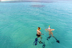 Snorkel in turquoise water. view from top. Caucasian couple of tourists snorkel in crystal turquoise water near Maldives Island Royalty Free Stock Photos