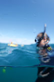 Snorkeler. Over-under picture split shot with water drops in the foreground and a woman wearing mask, snorkel and wetsuit in the background Royalty Free Stock Image