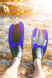 Snorkeler relaxing on a beach. Have a rest. Fins. Beach vacation snorkel. Relaxing on summer holidays lying down in water after sn Stock Image