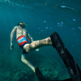 Snorkeling. Young man free diving and snorkeling on a lively reef Stock Images