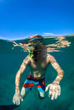 Snorkeling. Young man free diving and snorkeling on a lively reef royalty free stock image