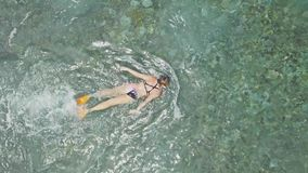 Snorkeling Above Reef Shallow Water Tropical Aerial 4k. Aerial footage of a girl snorkeling in a shallow water bay in Nusa Penida, Indonesia stock video