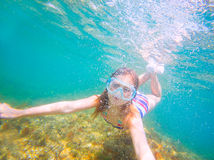 Snorkeling blond kid girl underwater goggles and swimsuit Royalty Free Stock Image
