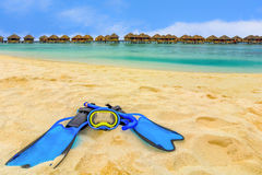 Snorkeling gear on the beach with water bungalows and the beach i Royalty Free Stock Photography
