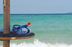 Snorkeling gear and sea. Snorkel and face mask on table next to turquoise sea Royalty Free Stock Photo