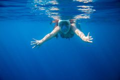 Snorkeling girl in full-face snorkeling mask undersea. Woman swimming. Warm shallow sea water coral reef. Underwater photo of oceanic landscape. Active seaside Royalty Free Stock Photography