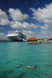 Snorkeling Lady on a Cruise. A woman snorkels near a cruise ship Stock Image