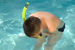 Snorkeling, looking for fish. Young boy looking underwater for some fish while snorkeling Royalty Free Stock Photo