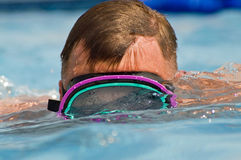 Snorkeling Man. Close up image of a man swimming in a pool while wearing a scuba mask royalty free stock images