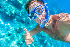 Snorkeling man underwater giving thumbs up. Ok signal wearing snorkel and mask having fun on beach summer holidays vacation enjoying recreational leisure time Royalty Free Stock Photos