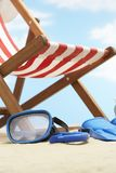 Snorkeling mask and flippers under deckchair on beach Royalty Free Stock Photography