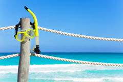 Snorkeling mask hanging on the wooden pier stake Royalty Free Stock Image