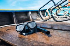 Snorkeling mask placing on a wooden boat sailing into the sea. Stock Photos