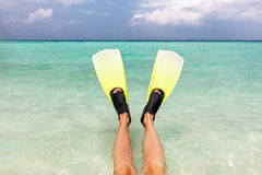 Snorkeling in the ocean. Fins on legs in clear water, Maldives. Stock Images