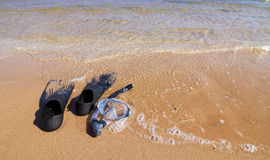 Snorkeling set lying on sand partly in sea water Royalty Free Stock Photography