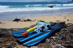 Snorkeling, Swimming, Diving Equipment on the rock beach. Snorkeling Equipment (blue flippers, yellow snorkel and transparent diving mask) on the rock beach Royalty Free Stock Photography