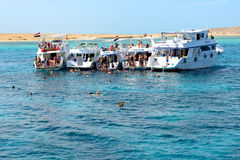 Snorkeling tourists and motor yachts Stock Photography