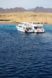 Snorkeling tourists and motor yachts on Red Sea in Ras Muhammad National Park Royalty Free Stock Images