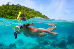 Snorkeling. Underwater portrait of a woman snorkeling in tropical sea. Splitted image with sky and green island Royalty Free Stock Photo