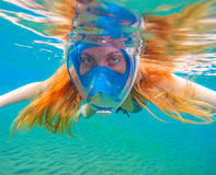 Snorkeling woman with bright red hair. Snorkel in full face mask. Stock Photography