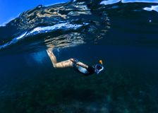 Snorkeling woman dives to sea bottom. Snorkeling girl in full-face snorkeling mask. Stock Image