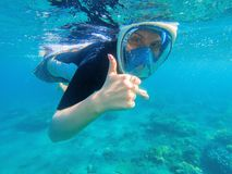 Snorkeling woman shows thumb. Snorkeling girl in full-face snorkeling mask. Stock Photography