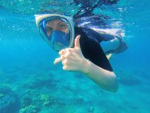 Snorkeling woman shows thumb. Snorkeling girl in full-face snorkeling mask. Royalty Free Stock Photo