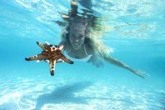 Snorkeling. Woman is snorkeling underwater, showing starfish Royalty Free Stock Photo