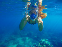 Snorkeling woman underwater showing thumbs. Snorkel in full face mask. Female swimmer with loose red hair. Beautiful girl in water. Underwater photo shot in Stock Photo