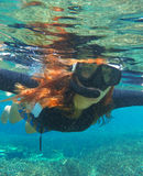 Snorkeling woman in water. Loose hair pretty girl swimming in the sea. Stock Photos