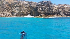 Snorkelling clear blue water in front of cliff Royalty Free Stock Image