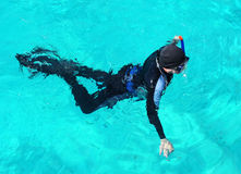 Snorkelling diver. A snorkeler swims on the surface of crystal clear water Stock Photography