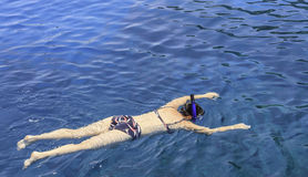 Snorkelling. Girl swimming in the sea with masks Royalty Free Stock Image