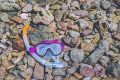 Snorkla för snorkelvatten för maskeringen det torra kugghjulet för sportar på havet för stenstrandkustlinjen koppla av signalen f Arkivfoto
