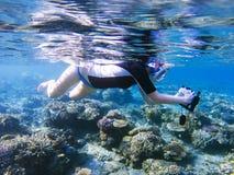 Snorkla flickan med den undervattens- kameran i korallrev Snorkel med kameran i undervattens- hus Royaltyfri Fotografi