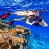 Snorkla i det tropiska vattnet med kameran Royaltyfria Foton