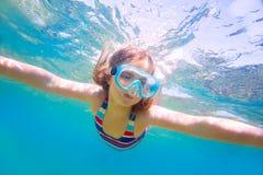 Snorkla skyddsglasögon och baddräkten för blond ungeflicka undervattens- Arkivbild