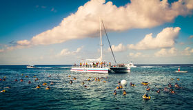 Snorkling Of The Coast of Cozumel Mexico. A boat filled with tourists, swimmers and snorkelers enjoying the water and beach resort life Royalty Free Stock Image