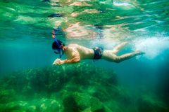 Snorkling man swim underwater. In turquoise sea Stock Images