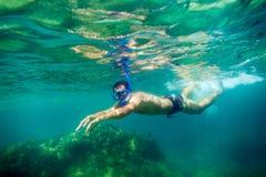 Snorkling man swim underwater. In turquoise sea Royalty Free Stock Photos