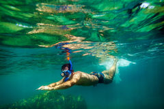 Snorkling man swim underwater. In turquoise sea Royalty Free Stock Photography
