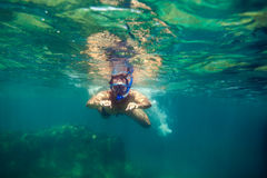 Snorkling man swim underwater. In turquoise sea Royalty Free Stock Images